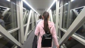Fille de touristes marchant sur un couloir bien allumé à l'avion d'aéroport clips vidéos