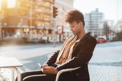 Fille de touristes noire en café de rue avec le smartphone Photos stock