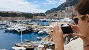 Fille de touristes prenant la photo des yachts dans le port maritime méditerranéen, utilisant le smartphone banque de vidéos