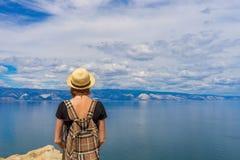 Fille de touristes de tween attrayant la position de chapeau et de sac ? dos sur le dessus de falaise et en admirant le beau pays images stock