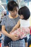 Fille de transport de mère chinoise asiatique à l'intérieur d'un transit de MRT Images libres de droits