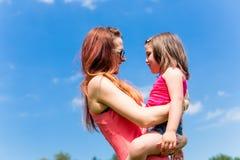 Fille de transport de mère sur son bras Photos stock
