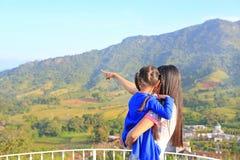 Fille de transport de mère asiatique de vue arrière sur le balcon au flanc de coteau et à préciser cela de voir photos libres de droits