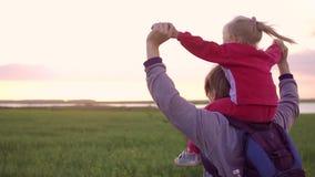 Fille de transport de père sur ses épaules et jeux avec elle Pendant le coucher du soleil dans un domaine clips vidéos