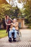Fille de travailleur social avec l'homme supérieur dans le fauteuil roulant Photo stock