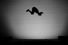 Fille de tremplin de silhouette effectuant le saut périlleux Image libre de droits