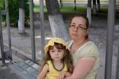 fille de trois ans en jaune avec sa mère Image stock