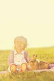 Fille de trois ans s'asseyant avec le lapin sur le pré Image libre de droits