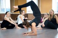 Fille de yogi faisant la pose Vrischikasana de scorpion d'asana dans la classe Photo libre de droits