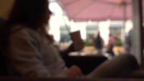 Fille Defocused de brune ayant sa boisson avec une paille dans un café par la fenêtre Tir de bokeh de fond de mouvement lent banque de vidéos