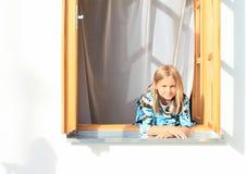 Fille derrière la fenêtre Photographie stock