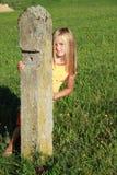 Fille derrière le poteau d'amarrage en pierre Photo libre de droits
