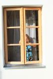 Fille derrière la fenêtre Photo stock