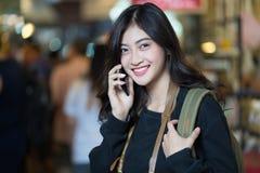 Fille descendant la rue parlant au téléphone portable sur un blurre image stock