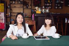 Fille deux à l'appareil-photo à un café Image stock