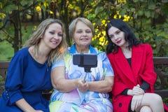 Fille deux avec la vieille mère prenant le selfie par le téléphone avec le monopod Photographie stock libre de droits