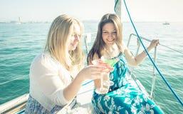 Fille deux ayant l'amusement sur le bateau avec des cocktails Photos libres de droits