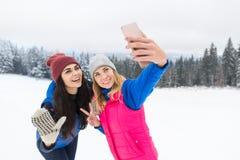 Fille deux prenant la photo de Selfie sur la neige futée d'hiver de jeune femme de montagne de Milou de téléphone Images libres de droits