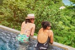 Fille deux se reposant dans l'eau de piscine Photos libres de droits
