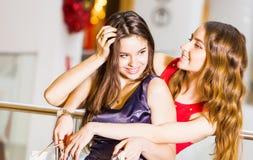 Fille deux se tenant avec des sacs dans des robes étreignant et riant du mail Concept de bonheur, achats, amitié Images stock