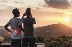 Fille deux se tenant sur un haut, étreignant et prenant la photo du coucher du soleil photo libre de droits