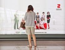 Fille devant l'annonce à l'aéroport de Pékin Capitl Internationl Photo stock
