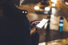 Fille dirigeant le doigt sur le smartphone d'écran sur la lumière de bokeh de fond dans la rue atmosphérique de ville de nuit, ut photographie stock libre de droits