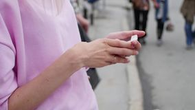Fille dirigeant son doigt sur l'?cran de smartphone sur le fond de la ville et des personnes, hippies, utilisant un mobile clips vidéos
