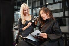 Fille discutant la coupe de cheveux avec son coiffeur féminin dans le salon de coiffure photo libre de droits