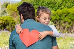 Fille donnant à papa une carte de coeur Photo stock