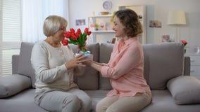 Fille donnant les tulipes et la boîte actuelle à la mère, félicitations de vacances, amour banque de vidéos