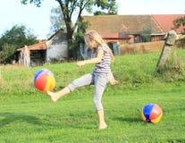 Fille donnant un coup de pied gonflant des boules Photos libres de droits