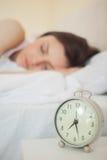 Fille dormant dans son lit avec un réveil sur le premier plan Image stock
