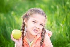 Fille douce avec un toth tombé tenant une pomme dans sa main images libres de droits