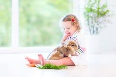 Fille douce d'enfant en bas âge avec les cheveux bouclés avec le vrai lapin Photos stock