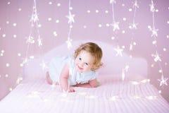 Fille douce d'enfant en bas âge jouant sur un lit entre Noël doux chaud l Image stock