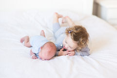 Fille douce d'enfant en bas âge soutenant son frère nouveau-né photo stock