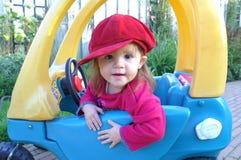 Fille douce dans le véhicule de jouet Photo stock