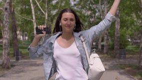 Fille drôle avec de longues promenades de cheveux en bas de la rue et écouter drôle de danses la musique sur des écouteurs Mouvem clips vidéos
