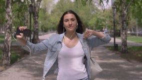Fille drôle avec de longues promenades de cheveux en bas de la rue et des danses écoutant la musique sur des écouteurs Mouvement  banque de vidéos