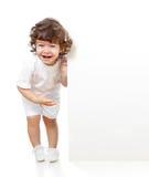 Fille drôle bouclée retenant le drapeau de publicité blanc Images libres de droits