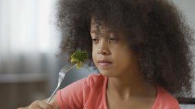 Fille drôle d'Afro-américain mangeant du brocoli avec dégoût, nourriture saine, suivant un régime clips vidéos