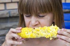 Fille drôle d'enfant en bas âge mangeant du maïs Image libre de droits
