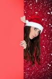 Fille drôle de Santa, panneau-réclame blanc et neige Photographie stock libre de droits