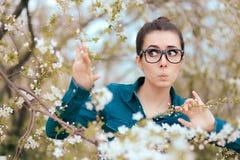 Fille drôle entourée par les arbres de floraison effrayés des allergies images libres de droits