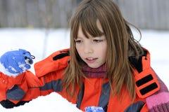 Fille drôle jouant avec la neige image stock