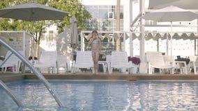 Fille drôle mignonne avec deux tresses dans le costume de natation sautant dans la piscine et éclaboussant l'amusement dans l'eau banque de vidéos