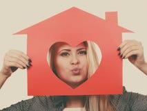 Fille drôle tenant la maison de papier rouge avec la forme de coeur photos stock