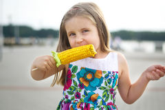 Fille drôle adorable mangeant l'épi de maïs photographie stock libre de droits