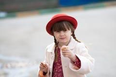 Fille drôle avec des tresses dans le chapeau mangeant la crème glacée  Photos libres de droits